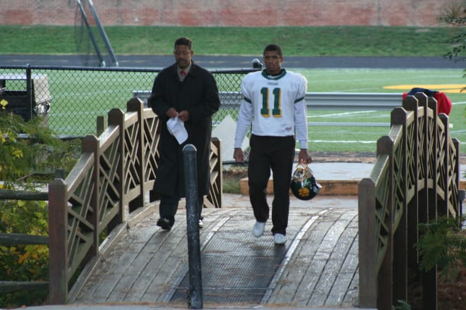 Former NC State Wolfpacker quarterback Russell Wilson walks off the high school field with his father.