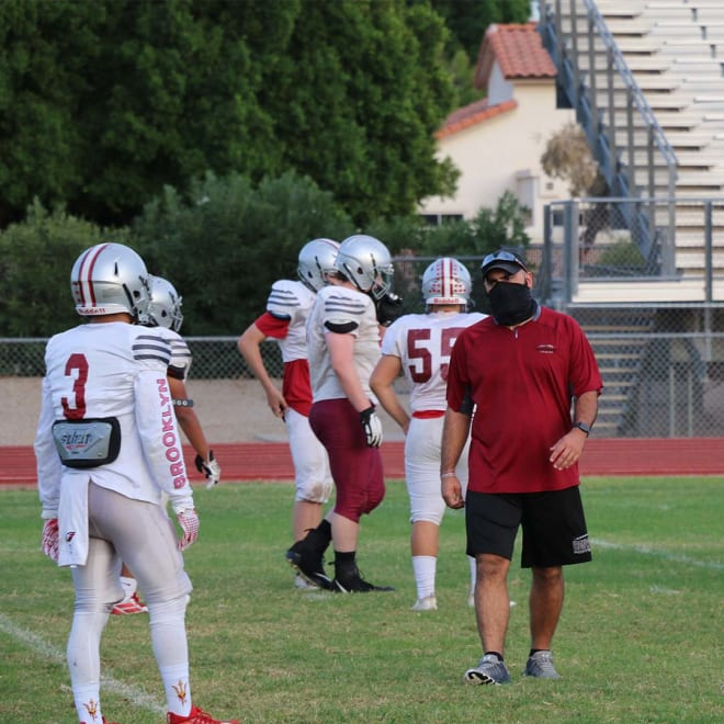 Chris Rizzo (right) gives advice at a Ironwood football practice.