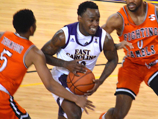 ECU's Tremont Robinson-White drives on Campbell's Trey Spencer and Messiah Thompson in Saturday's game in Greenville.