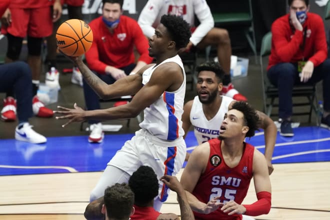Boise State guard Devonaire Doutrive, left, drives to the basket over SMU forward Ethan Chargois (25) during the first half of an NCAA college basketball game in the first round of the NIT, Thursday, March 18, 2021, in Frisco, Texas.