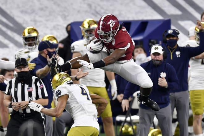Alabama running back Najee Harris hurdles Notre Dame defensive back Nick McCloud during the Rose Bowl game. Photo | Getty Images
