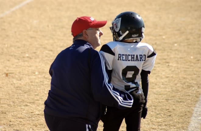 The late Gary Reichard, left, talks to his son Will during a pee-wee football game. Photo courtesy of Dana Reichard