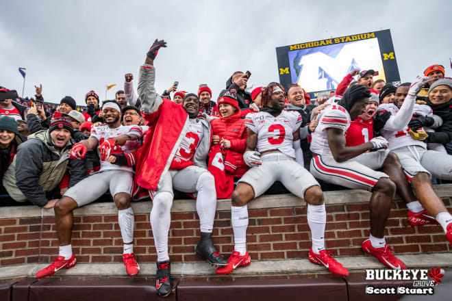 Ohio State players celebrate with Buckeye fans at Michigan Stadium.