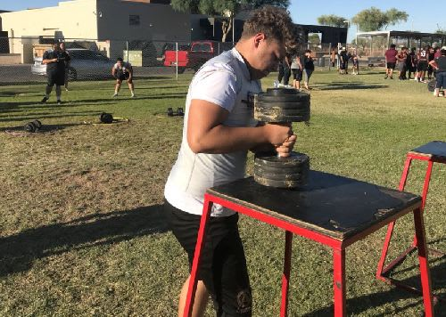 Copper Canyon senior lineman Josh Kauffman lifts the dumbbell from a table before running and placing it in a hoop during the obstacle course.  The Aztecs begin the 2018 season on Aug. 24 with a home game against Liberty in Glendale.