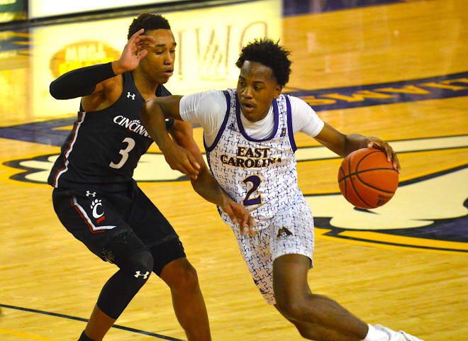 Tristen Newton drives on Mika Adams-Woods in ECU's 70-67 overtime loss to Cincinnati on Sunday in Greenville