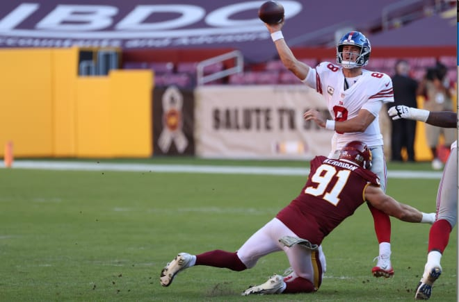 New York Giants quarterback Daniel Jones (8) passes the ball while being hit by Washington Football Team defensive end Ryan Kerrigan (91) in the third quarter at FedExField.