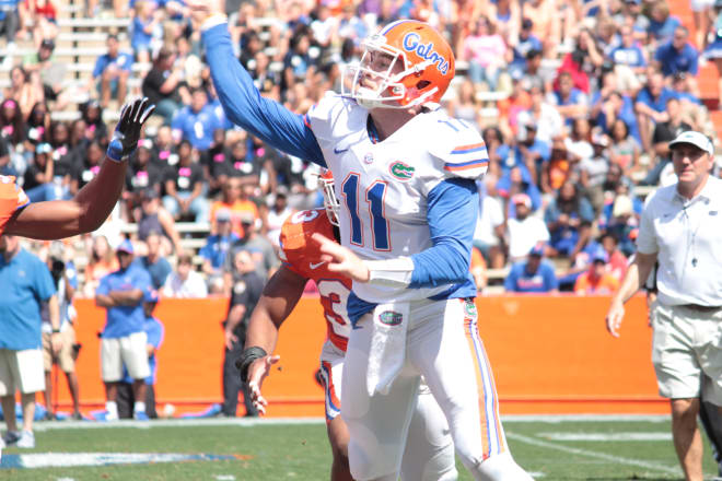 Florida quarterback Kyle Trask makes a throw while Dan Mullen looks on.