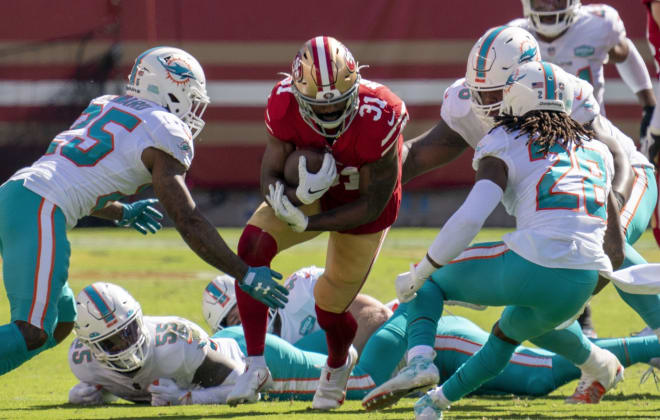 San Francisco 49ers running back Raheem Mostert (31) is tackled by Miami Dolphins cornerback Xavien Howard (25) and strong safety Bobby McCain (28) during the second quarter at Levi's Stadium.