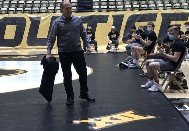 Brian Smith unveils a Big XII logo on Mizzou's mat at the Hearnes Center Thursday afternoon