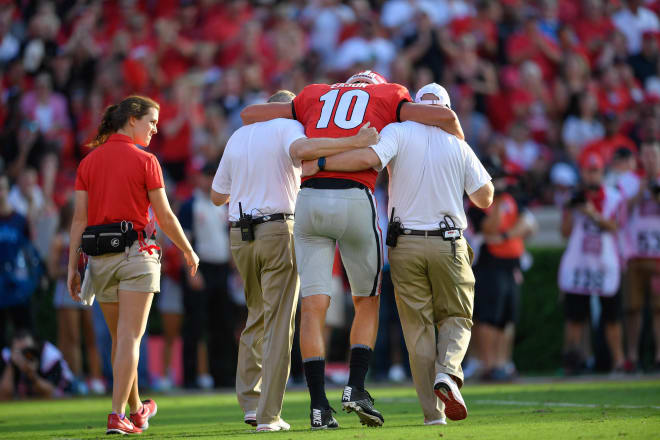 Georgia Bulldogs quarterback Jacob Eason (10) is helped off the field after being injured against the Appalachian State Mountaineers during the first quarter at Sanford Stadium. Photo  Credit: Dale Zanine-USA TODAY Sports