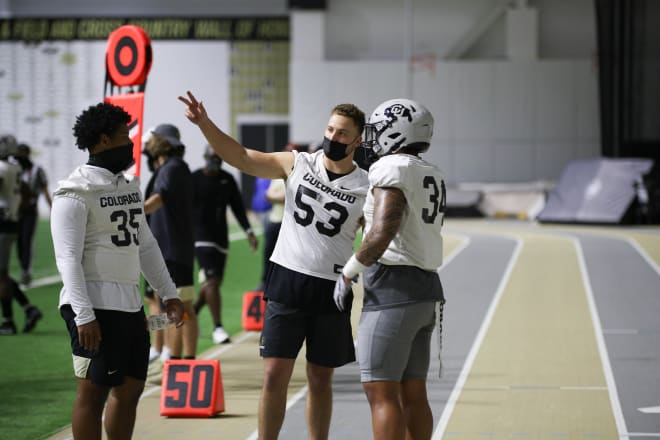 Senior inside linebacker Nate Landman shares a word with freshmen ILBs Mister Williams and Zephaniah Maea