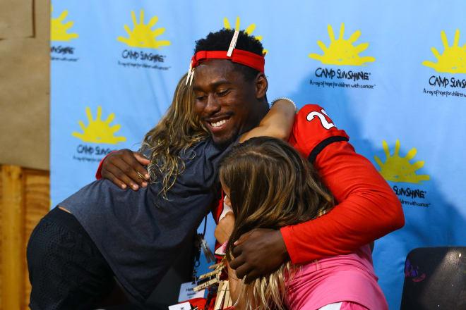 J.R. Reed hugs two campers at Camp Sunshine (photo: UGA Athletics)