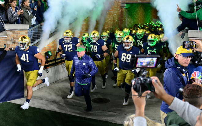 Notre Dame football head coach Brian Kelly leading the team onto the field