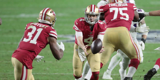 San Francisco 49ers quarterback Nick Mullens (4) pitches the ball to running back Raheem Mostert (31) against the Buffalo Bills during the third quarter at State Farm Stadium.