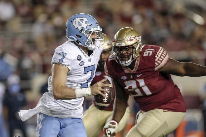 Defensive lineman Robert Cooper chases UNC quarterback Sam Howell.
