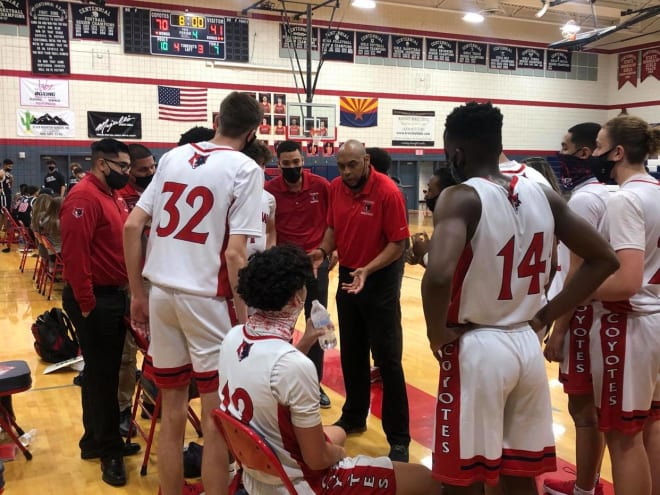 Coach Randy Lavender (middle) speaks to his players in a Centennial Coyotes boys basketball huddle.