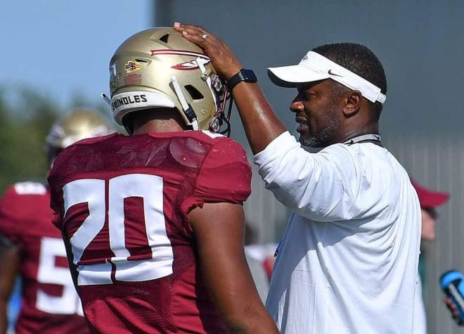 FSU coach Willie Taggart shares a few words with freshman linebacker/safety Jaiden Woodbey.