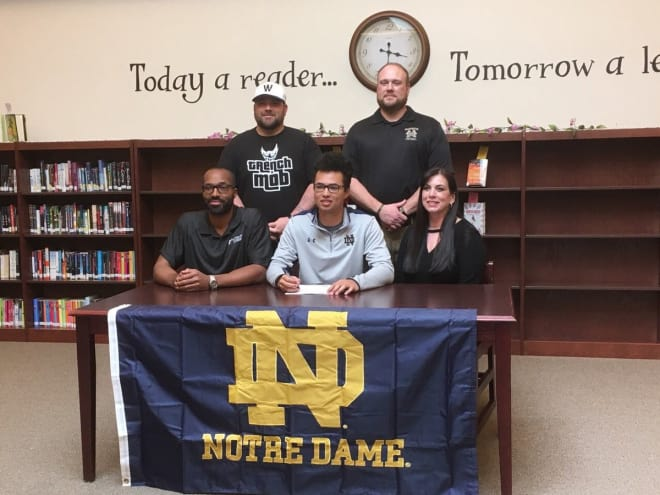 Marcus Thorne (signing in the center) carries on the legacy of his father (left), who played for Lou Holtz from 1993-95.