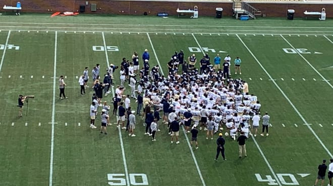 The team huddles on Coach Collins after the scrimmage/practice