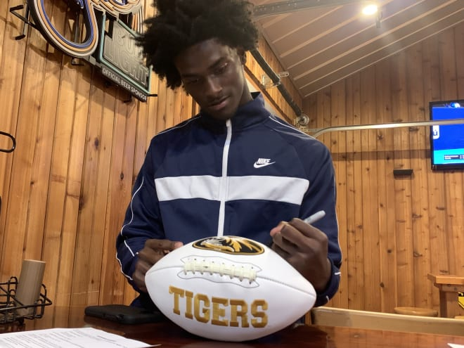 Rakestraw signs a football that will be put on sale on hornsdownshop.com.