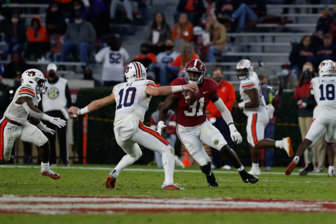 Auburn quarterback Bo Nix (10) is pursued by Alabama outside linebacker Will Anderson Jr. Photo | Getty Images