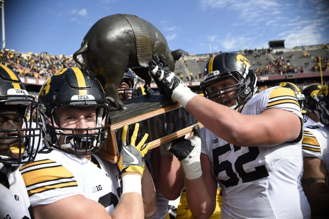 Iowa players carry the Floyd of Rosedale Trophy in 2016.